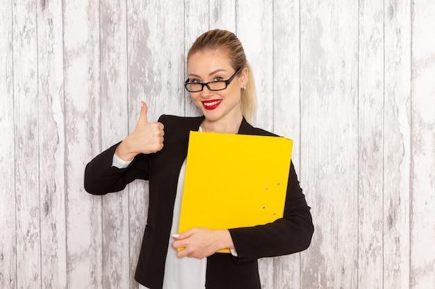 Vooraanzicht jonge zakenvrouw in strikte kleren zwarte jas met bestanden en documenten op wit oppervlak