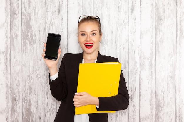 Vooraanzicht jonge zakenvrouw in strikte kleren zwarte jas met documenten en telefoon op wit oppervlak