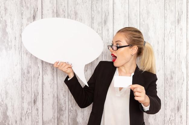 Vooraanzicht jonge zakenvrouw in strikte kleren zwarte jas met enorme witte bord en kaart op wit oppervlak