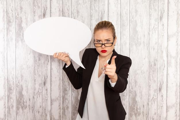 Vooraanzicht jonge zakenvrouw in strikte kleren zwarte jas met enorme witte bord op wit oppervlak