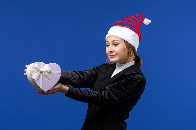 Vooraanzicht jongedame hartvormig aanwezig op de blauwe muur nieuwe jaar geschenken vakantie houden