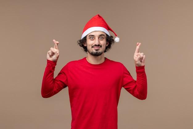 Vooraanzicht jongeman kruising zijn vingers op bruine achtergrond emoties kerstvakantie