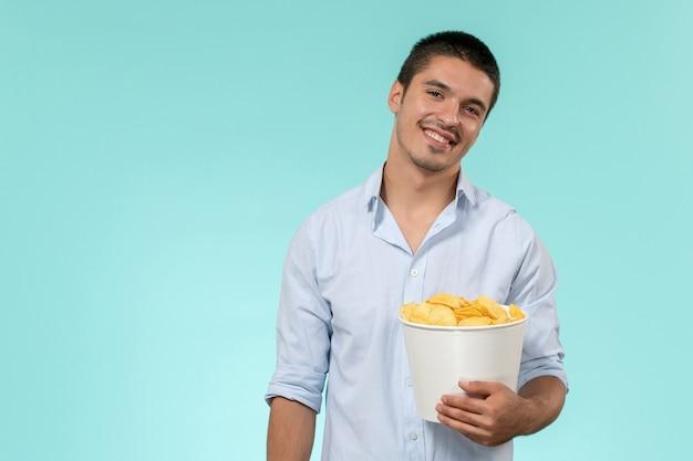 Vooraanzicht jongeman met aardappel cips en lachend op een blauwe muur eenzame afgelegen mannelijke filmbioscoop