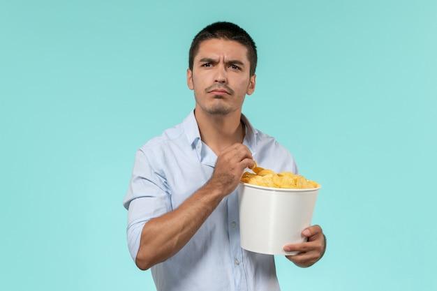 Vooraanzicht jongeman met aardappel cips tijdens het kijken naar film op de blauwe muur eenzame afgelegen mannelijke filmbioscoop
