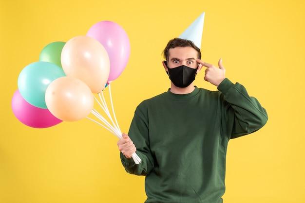 Vooraanzicht jongeman met feestmuts en kleurrijke ballonnen die vingerpistool tegen zijn tempel op gele achtergrond utting