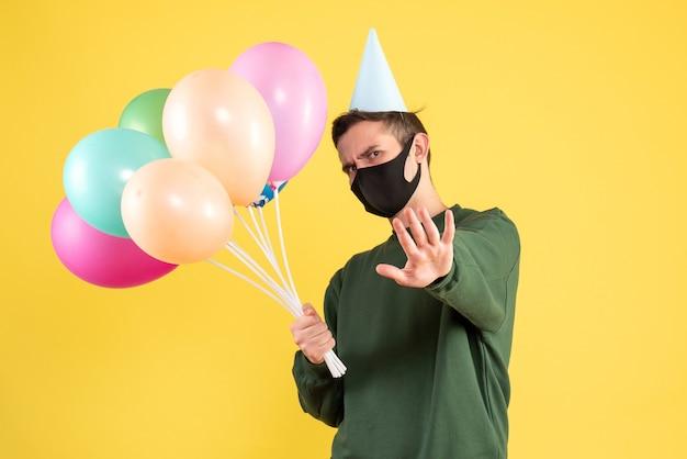 Vooraanzicht jongeman met feestmuts en kleurrijke ballonnen iets tegenhouden staande op gele achtergrond