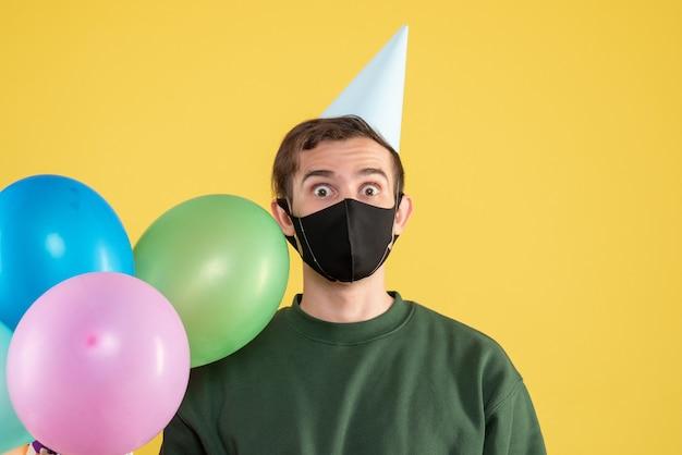 Vooraanzicht jongeman met feestmuts en zwart masker kleurrijke ballonnen op geel