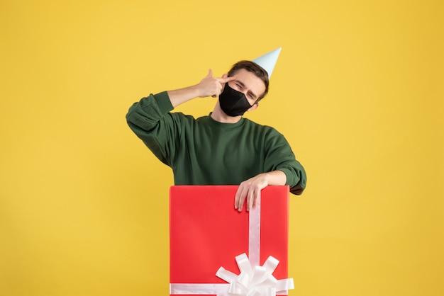 Vooraanzicht jongeman met feestpet en masker staande achter grote geschenkdoos op gele achtergrond