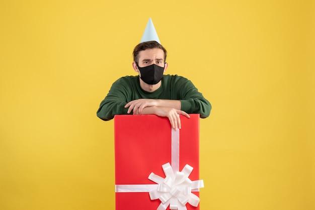 Vooraanzicht jongeman met feestpet en zwart masker achter grote geschenkdoos op geel