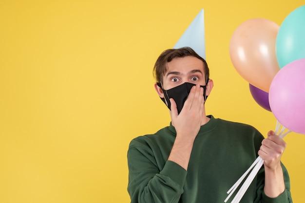 Vooraanzicht jongeman met feestpet en zwart masker met ballonnen op geel
