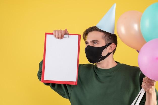 Vooraanzicht jongeman met feestpet en zwart masker met klembord en ballonnen op geel