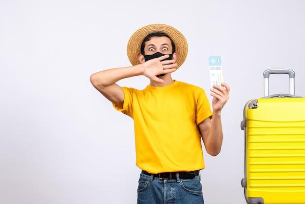 Vooraanzicht jongeman met grote ogen in geel t-shirt staande in de buurt van gele koffer vliegticket te houden