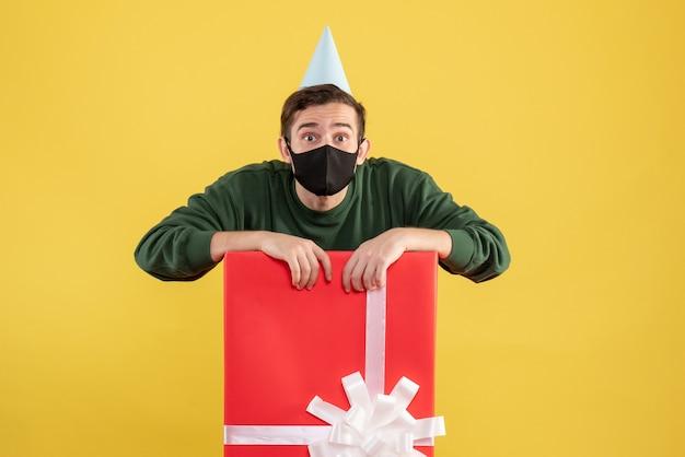 Vooraanzicht jongeman met grote ogen met feestmuts achter grote geschenkdoos op geel