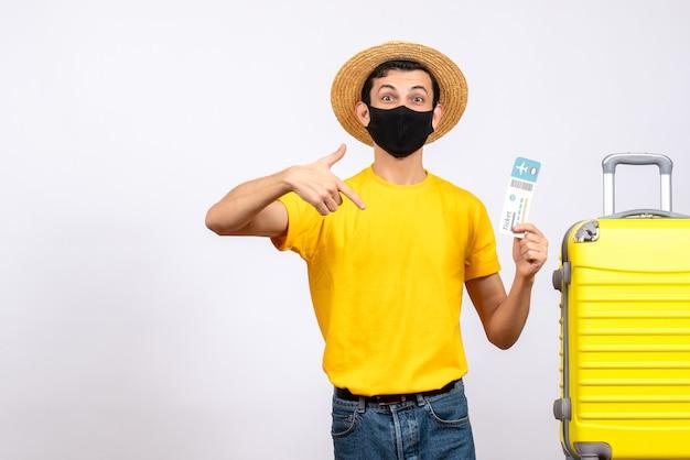 Vooraanzicht jongeman met grote ogen met strohoed die zich dichtbij gele koffer bevindt die vliegtuigticket richt