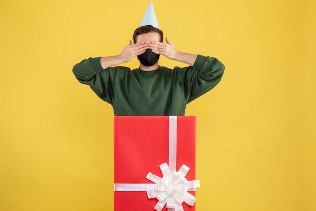 Vooraanzicht jongeman ogen sluiten met handen achter grote geschenkdoos op geel