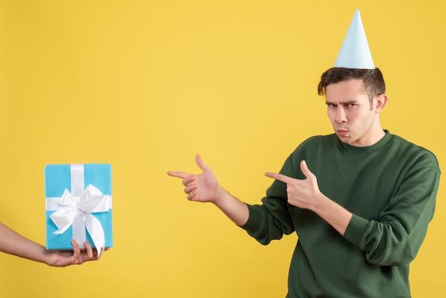Vooraanzicht jongeman wijzend op geschenk in menselijke hand op geel