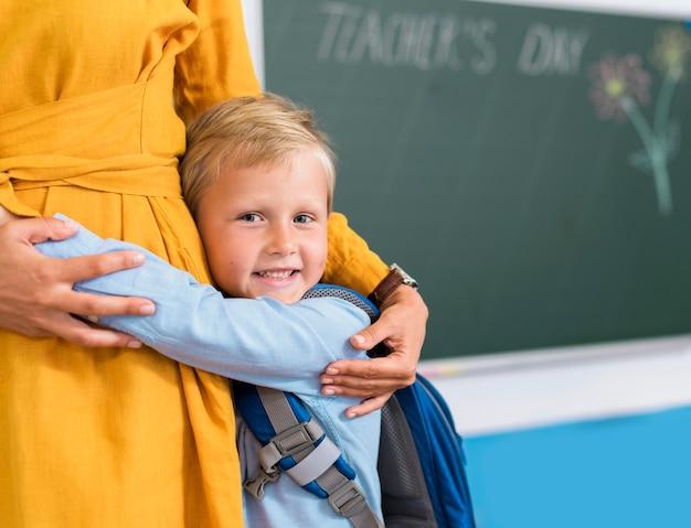 Vooraanzicht jongen knuffelen zijn leraar met kopie ruimte