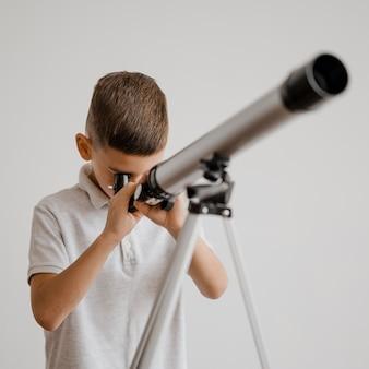 Vooraanzicht jongen met een telescoop in de klas
