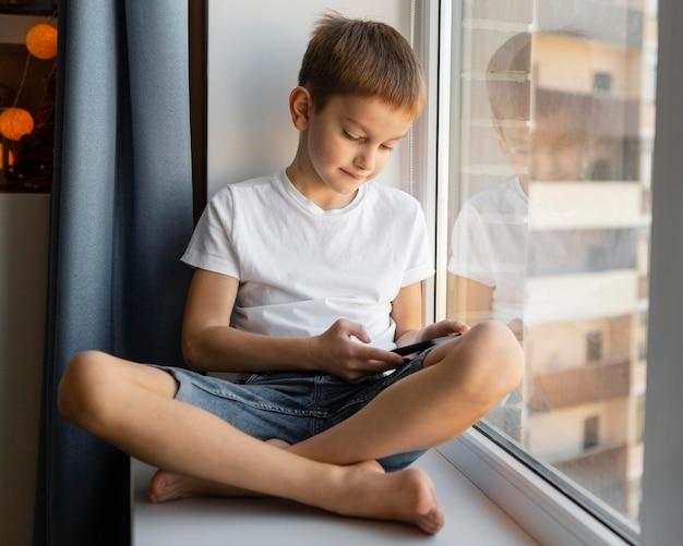 Vooraanzicht jongen zit naast het raam