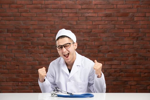 Vooraanzicht juichende mannelijke arts in witte medische pak