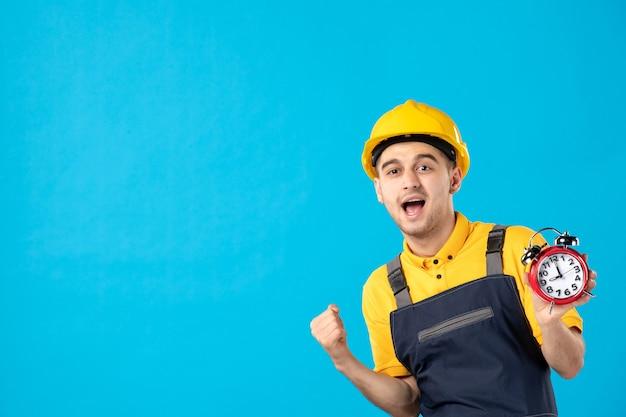 Vooraanzicht juichende mannelijke werknemer in geel uniform met klokken op blauw