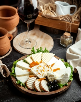 Vooraanzicht kaasplateau met een glas rode wijn