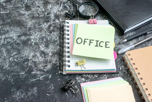 Vooraanzicht kantoor geschreven notitie met kleurrijke stickers en voorbeeldenboek op grijze ondergrond kleur baan college business school team kantoor foto werk