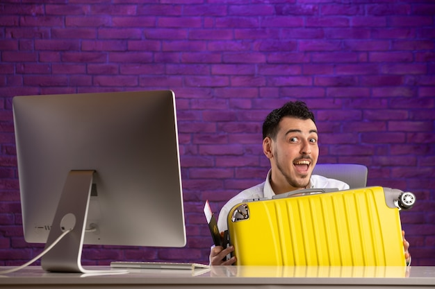 Vooraanzicht kantoormedewerker zit achter zijn werkplek met kaartjes en paspoort