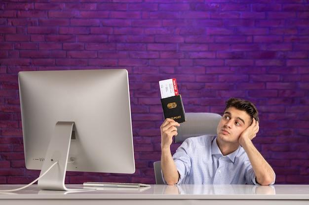 Vooraanzicht kantoormedewerker zit achter zijn werkplek met paspoort en kaartjes