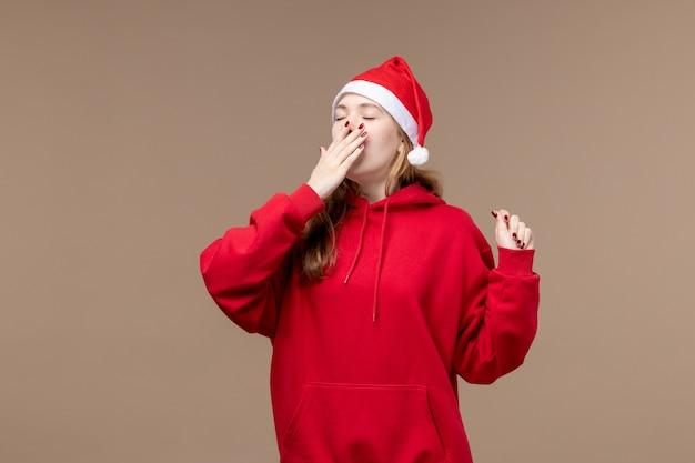 Vooraanzicht kerst meisje geeuwen op een bruine achtergrond vrouw vakantie kerst