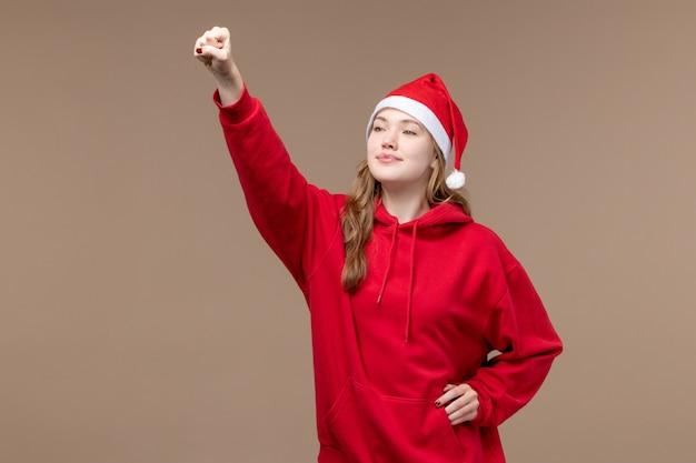 Vooraanzicht kerst meisje glimlachend en groet op bruine achtergrond vrouw vakantie kerst