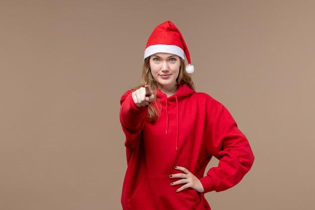 Vooraanzicht kerst meisje glimlachend en wijzend op bruine achtergrond vrouw vakantie kerst
