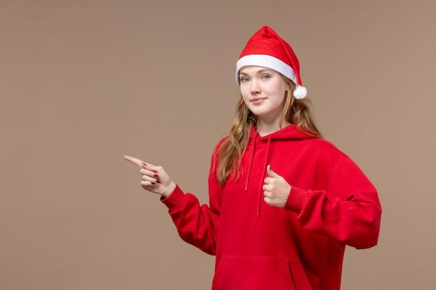 Vooraanzicht kerst meisje met kalm gezicht op bruine achtergrond vrouw vakantie kerst emotie