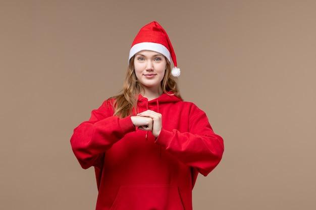 Vooraanzicht kerst meisje met opgetogen gezicht op bruine achtergrond vrouw vakantie kerst