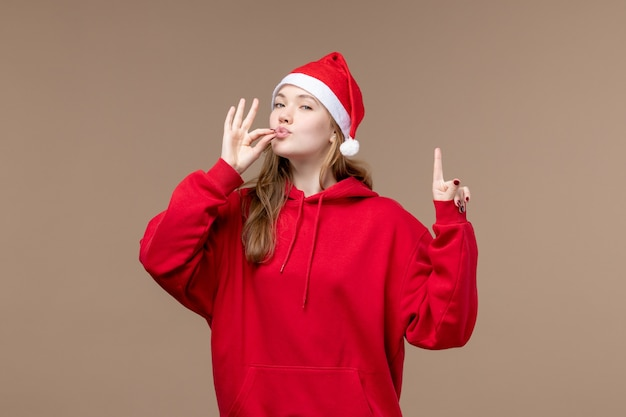 Vooraanzicht kerst meisje met opgetogen uitdrukking op bruine achtergrond vrouw vakantie kerst