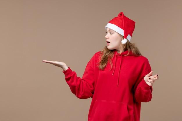 Vooraanzicht kerst meisje met verbaasd gezicht op bruine achtergrond vakantie nieuwjaar kerst