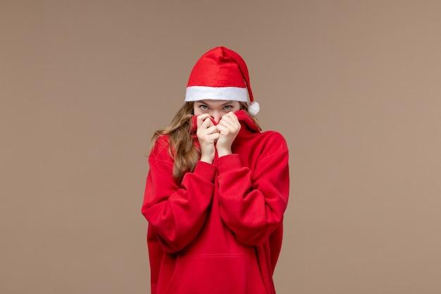 Vooraanzicht kerst meisje met verlegen gezicht op bruine achtergrond vrouw vakantie kerst