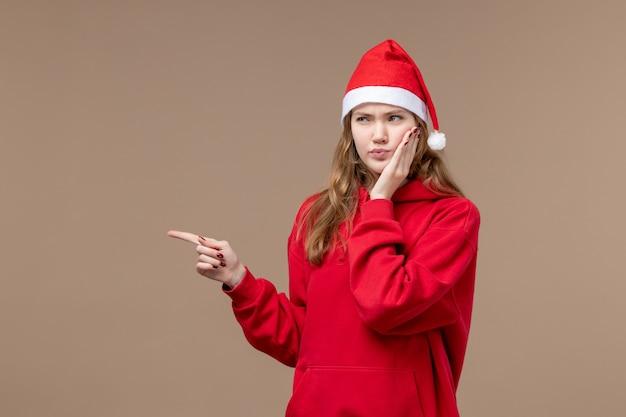 Vooraanzicht kerst meisje met verward gezicht op bruine achtergrond vakantie vrouw kerst emotie
