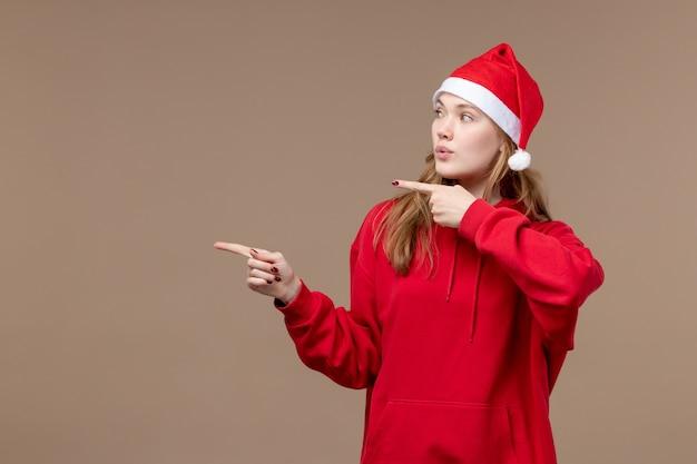 Vooraanzicht kerst meisje op bruine achtergrond vakantie vrouw kerst emotie