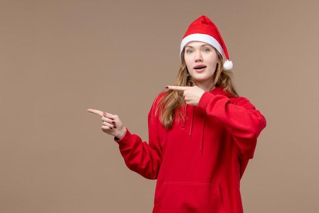 Vooraanzicht kerst meisje op bruine achtergrond vakantie vrouw kerst emoties