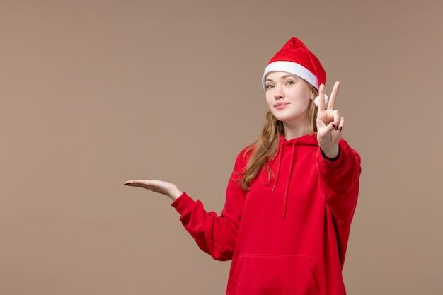 Vooraanzicht kerst meisje poseren op bruine achtergrond vakantie nieuwjaar kerst