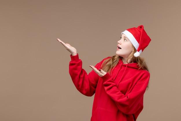 Vooraanzicht kerst meisje poseren op bruine achtergrond vrouw vakantie kerst emotie