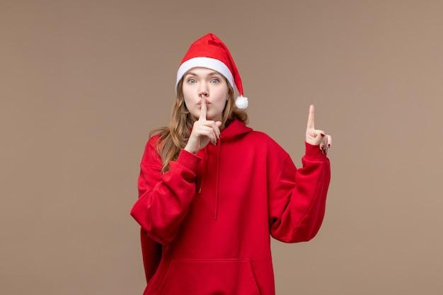 Vooraanzicht kerst meisje vraagt om stil te zijn op bruine achtergrond vrouw vakantie kerst