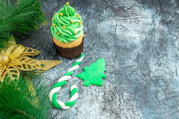Vooraanzicht kerstboom cupcake xmas candy xmas ornamenten op grijze achtergrond met kopie ruimte