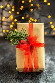 Vooraanzicht kerstcadeau op donkere kerstverlichting