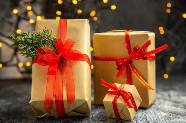 Vooraanzicht kerstcadeau vastgebonden met rood lint kerstverlichting op donker
