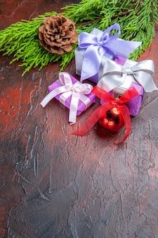 Vooraanzicht kerstcadeaus boomtak met kegel kerstboom speelgoed op donkerrode achtergrond kopie ruimte nieuwjaarsfoto