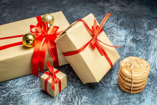 Vooraanzicht kerstcadeautjes met zoete koekjes op de licht-donker vakantie foto cadeau kerst kleur nieuwjaar