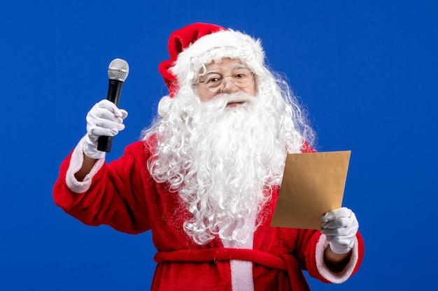Vooraanzicht kerstman die microfoon vasthoudt en brief leest op de blauwe nieuwjaarskleur vakantie kerstsneeuw