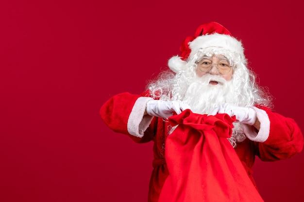 Vooraanzicht kerstman die rode zak vol cadeautjes voor kinderen opent op rode vakantie kerstemotie